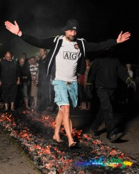 Firewalk charity event in aid of the peace hospice man in shorts walking on fire mark in time event photography