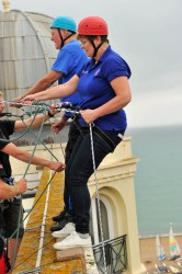 Two abseilers standing on the roof of The Grand Hotel Brighton